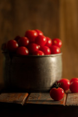 Vertical image of cherry tomatoes in a metal pail.