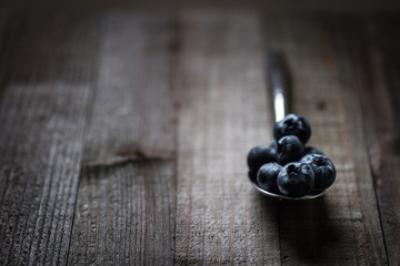 Blueberries in a spoon on a wooden surface.