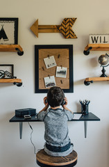 Rear view of boy with headphones sitting at desk