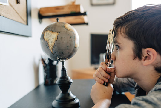 Side view of a boy looking at a globe with a magnifying glass