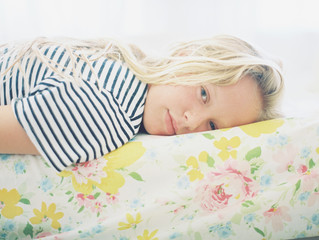 blonde girl tween in striped shirt on vintage floral sheet portrait