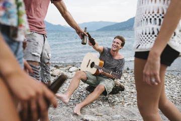 Group of friends toasting with beers on the beach