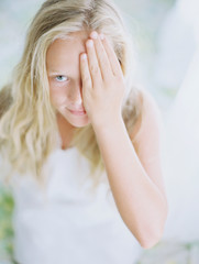 blonde girl with hand over eye in white dress on film