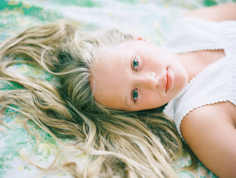 portrait of blonde girl wtih hair spread out on vintage floral sheets