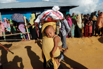 A Rohingya refugee woman walks carrying her baby after receiving food aid in a camp near Cox's Bazar