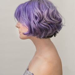Side view of purple hair woman against white background