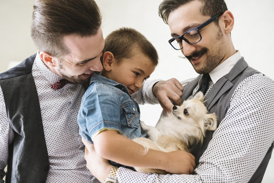 Happy gay male couple relaxing at home with their son