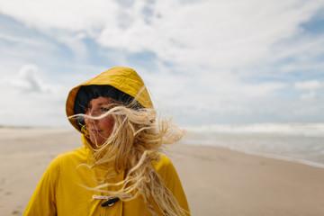 Woman on a windy beach wearing a yellow raincoat