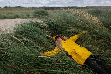 Woman hiding for the wind in the dunes while wearing a yellow raincoat