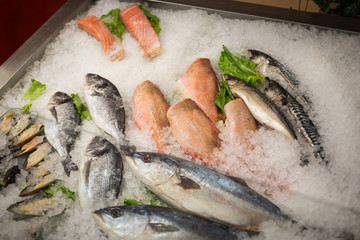 Photo sur Plexiglas Poisson High Angle Still Life of Variety of Raw Fresh Fish Chilling on Bed of Cold Ice in Seafood Market Stall,Fresh seafood on ice in the showcase,Salmon on cooled market display,Supermarket, fish department