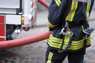 A member of the fire brigade holds a water supply hose from the fire engine