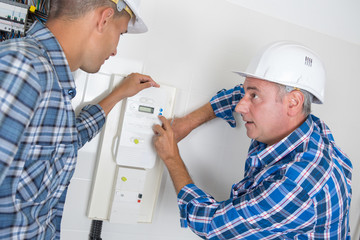 electrician explaining electric meter to apprentice