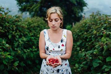 Woman holding a full hand of raspberries in raspberry field