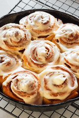 Close Up on Iced Cinnamon Buns or Rolls in Cast Iron Skillet on Cooling Rack