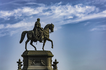 Statue of rider on horse. Monument in Germany under blue sky.