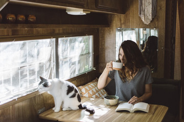 Woman reading and eating breakfast