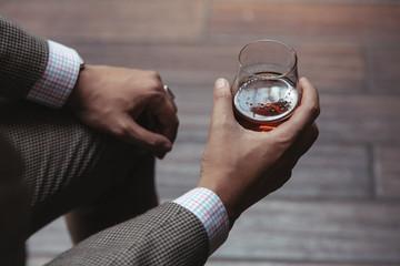 Dapper gentleman holding a glass of rum