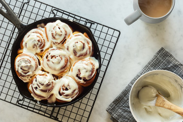 Iced Cinnamon Buns or Rolls Baked in Cast Iron Skillet with Coffee Mug on Counter