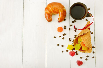 Cup of coffee, croissant, waffles and marmalade on wood white background.