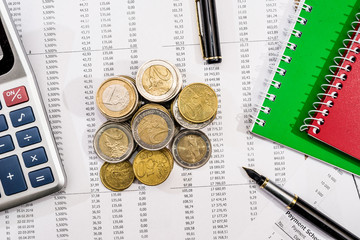 notepad, financial documents, calculator, pen and coin