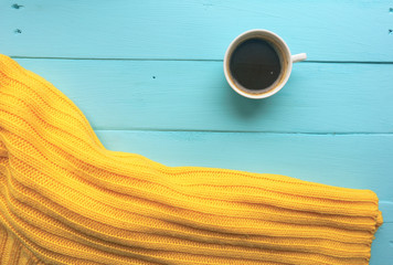 Cup of coffee and yellow sweater. Bright blue, turquoise surface. Painted Board. Close-up with copy space. Top view
