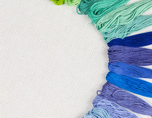 skeins of multicolored embroidery threads on white cotton canvas