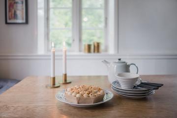 Kaffee und Kuchen wird neben brennenden Kerzen serviert