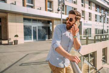 Young Caucasian businessman using phone in front of a corporate building.