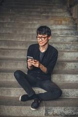 Young Asian man using phone outdoor.