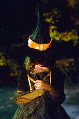 Young girl in witch costume in woods