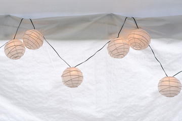 string of glowing paper lanterns on white background