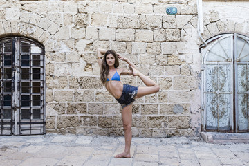 Young female yogi stretching on one leg by an old wall