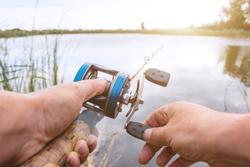 A man is fishing with a baitcasting reel. Hands, a rod and a baitcasting reel in the background of the rising sun