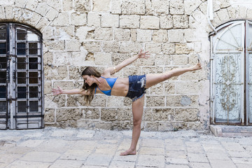 Young female yogi balancing on one leg by an old wall
