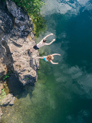 Overhead drone image of teenagers jumping off a rock