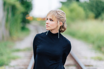 Beautiful young woman standing by train tracks