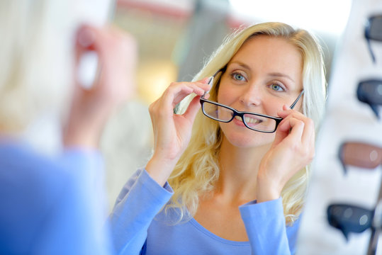 young woman trying on glasses with black rims