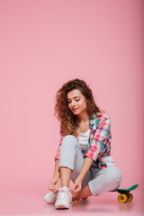 Young lady sitting on skateboard and tie shoelaces isolated