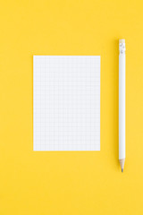 White pencil and note card on yellow background