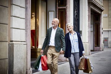 Senior Couple With Shopping Bags On Sidewalk