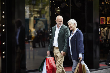 Senior Couple With Shopping Bags By Store
