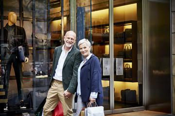 Smiling Senior Couple Standing Outside Store