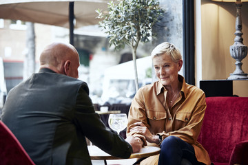 Senior Woman Holding Man's Hand In Restaurant