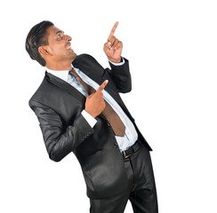 Businessman in black suit pointing happily over white background