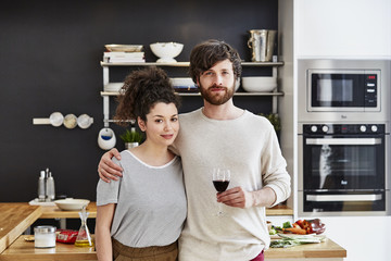 Couple Holding Wineglass In Kitchen