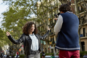 Man Photographing Woman In City