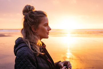 side profile portrait of young woman at sunset on beach