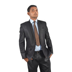 Portrait of a young businessman in black suit, hands in pocket over white background