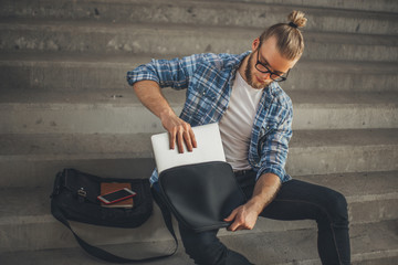 Young Blonde Man taking his computer out of his bag.