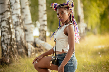 people, photography, technology, leisure and lifestyle - happy young african american female photographer looking to vintage camera